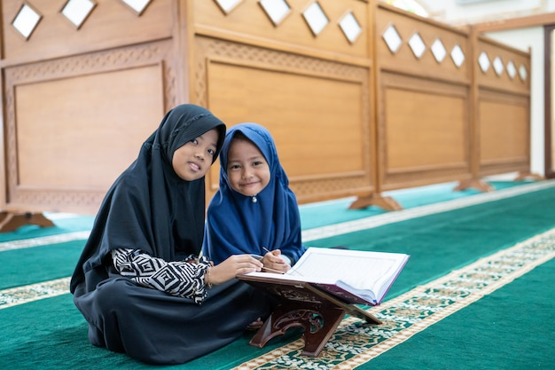Criança asiática muçulmana lendo o alcorão