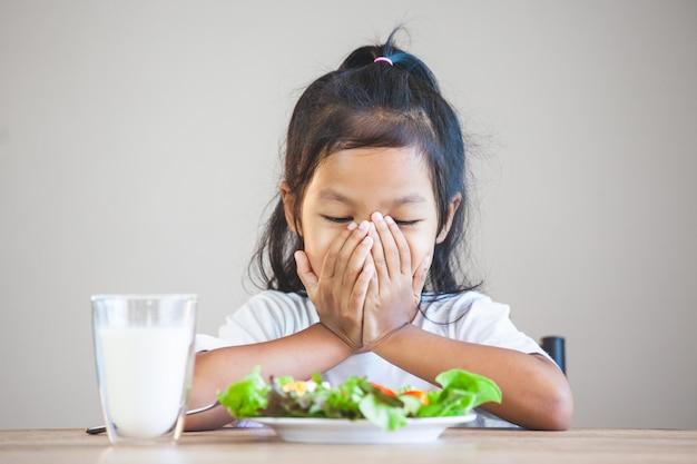 Criança asiática não gosta de comer legumes e se recusam a comer vegetais saudáveis