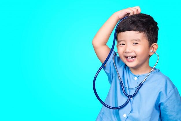 Criança asiática no uniforme médico azul que guarda o estetoscópio.