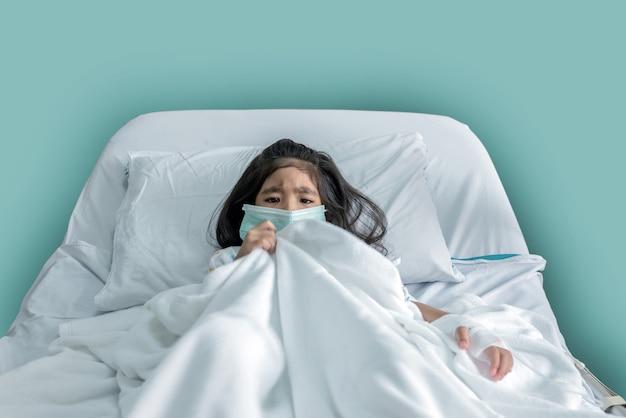 Criança asiática paciente com máscara tem febre na cama do hospital