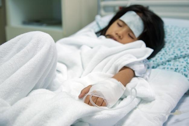 Criança asiática patien dormindo na cama de hospital com tratamento medicamentoso