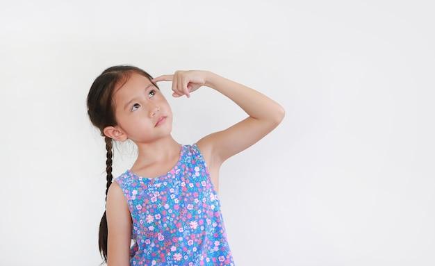 Criança asiática pensando e apontando o dedo indicador para a cabeça