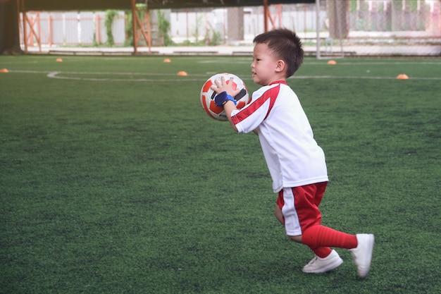 Criança asiática pequena sorridente do jardim de infância de 4 anos, jogador de futebol em uniforme de futebol está jogando futebol na sessão de treinamento, exercícios de futebol para crianças, foco seletivo, desfoque de movimento a pé