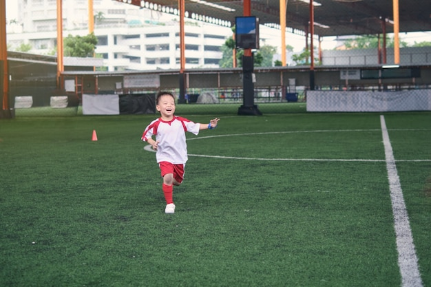 Criança asiática pequena sorridente do jardim de infância de 4 anos, jogador de futebol em uniforme de futebol está jogando futebol na sessão de treinamento, exercícios de futebol para crianças, foco seletivo