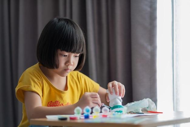 Criança asiática pintar a cor no papel, o conceito de educação
