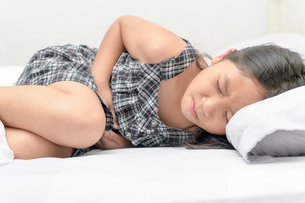 Criança asiática que sofre de dor de estômago