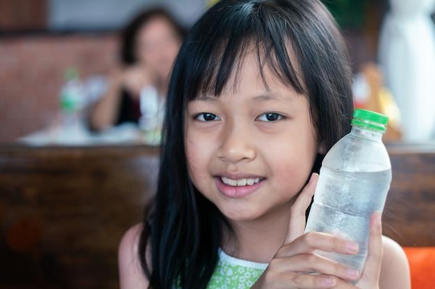 Criança asiática segurando e bebendo bebida gelada no restaurante