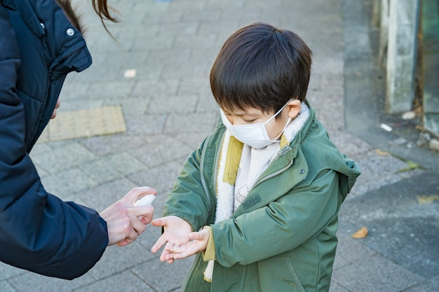 Criança asiática sendo esterilizada por spray em movimento ao ar livre