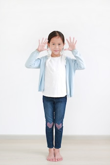 Criança asiática sorridente mostrando dez dedos em pé