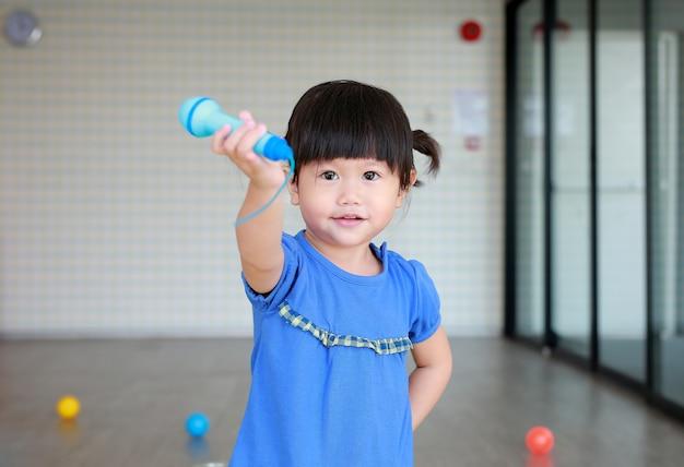 Criança asiática tocando microfone de plástico no quarto do garoto