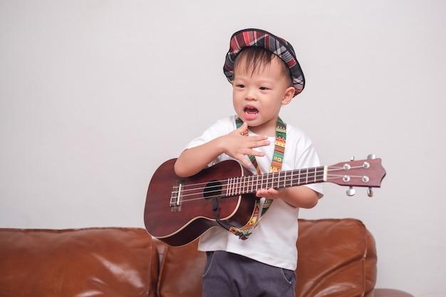Criança asiática, tocando violão havaiano