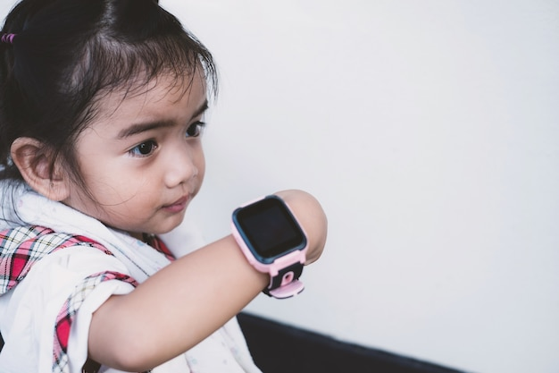 Criança asiática usa relógios inteligentes de tecnologia com rostos felizes.