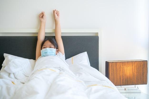 Criança asiática usando máscara acorda e estica o braço na cama pela manhã, conceito de saúde