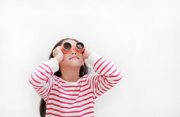 Criança asiática usando óculos de telescópio e olhando para cima em branco
