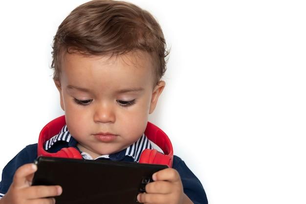 Criança assistindo vídeos no celular com fones de ouvido vermelhos e camisa azul escura