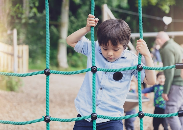 Criança ativa corda de escalada no parque infantil, criança desfrutando de atividade em um parque de aventura escalada em dia ensolarado de verão, menino bonitinho se divertindo em um parque infantil ao ar livre.