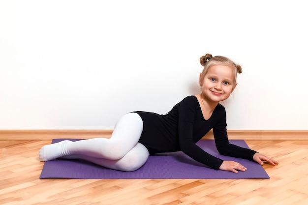 Criança atlética descansa em um tapete após o treino em casa