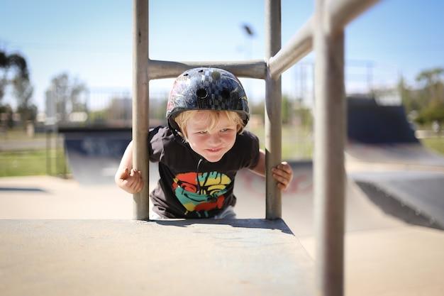 Criança australiana loira fofa e adorável com um capacete, brincando feliz no parquinho
