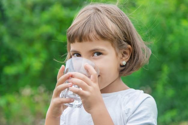 Criança bebe água de um copo