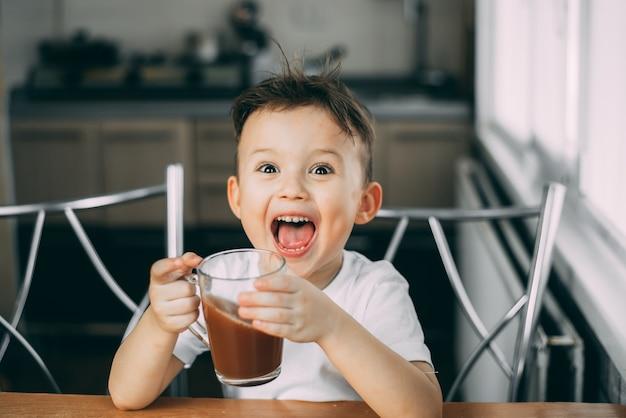 Criança bebe chocolate se contorcendo na cozinha durante o dia, segura uma caneca nas mãos e grita