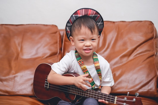 Criança bebê menino criança usando chapéu segurar & tocar guitarra havaiana ou ukulele na sala de estar
