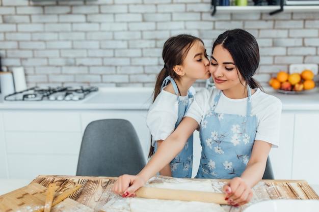 Criança beijando a irmã enquanto cozinha na cozinha