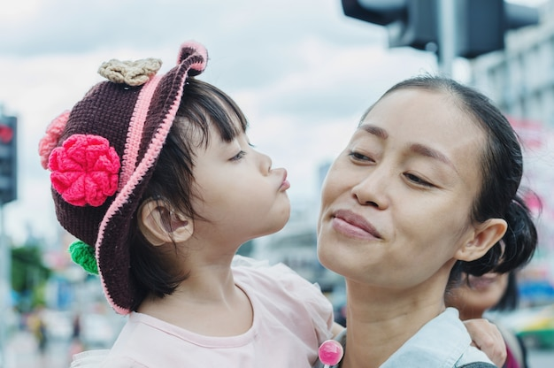 Criança beijando a mãe, mãe asiática e criança brincando com diversão.