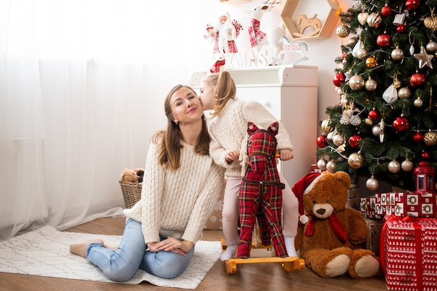 Criança beijando sua mãe em casa perto de caixas de árvore e presente de natal