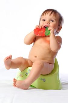 Criança bonita bebê senta-se no penico e mantém mordedor