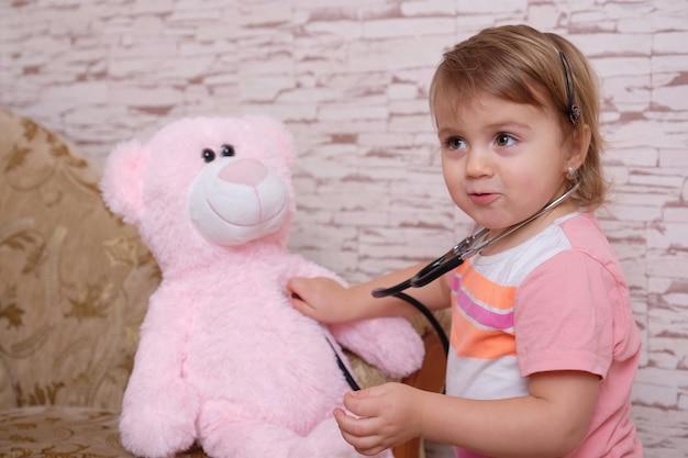 Criança bonita brincando de médico ou enfermeiro com brinquedos de pelúcia em casa.
