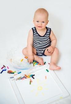 Criança bonita com criatividade desenha com giz de cera em casa em uma folha de papel branco. o conceito de desenvolvimento inicial da criatividade das crianças