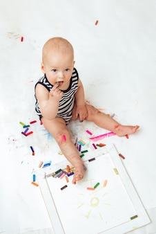 Criança bonita com criatividade desenha com giz de cera em casa em uma folha de papel branco. t