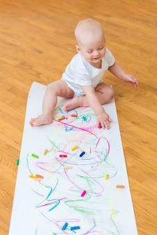 Criança bonita com criatividade desenha com giz de cera em casa em uma folha de papel branco.