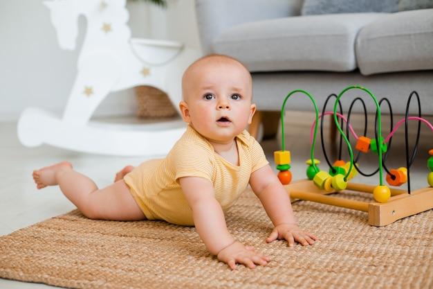 Criança bonita em traje amarelo fica em casa no chão brincando em um brinquedo em desenvolvimento. conceito de desenvolvimento infantil