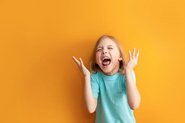 Criança bonita em uma parede laranja, 6-8 anos de idade, menina grita, indignada, não feliz