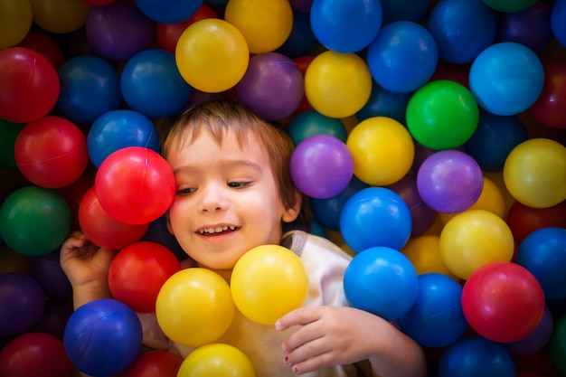 Criança bonita feliz jogando e se divertindo no jardim de infância com bolas coloridas