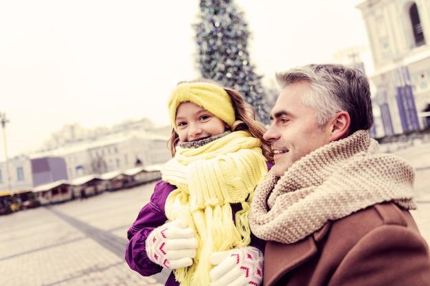 Criança bonita. menina encantada com um sorriso no rosto enquanto ouve o pai