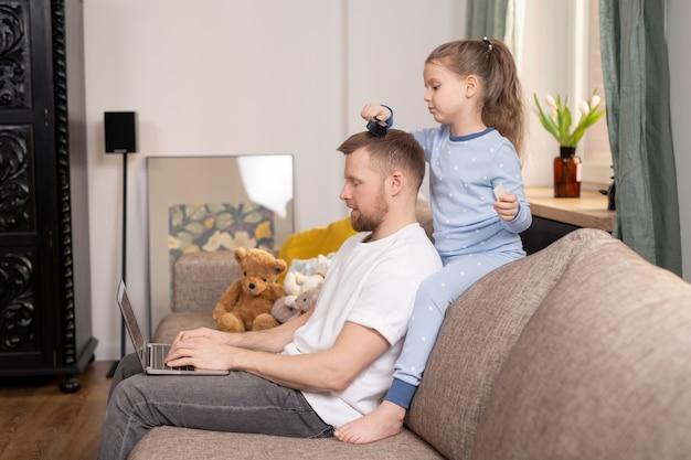 Criança bonita penteando o cabelo do pai em rede na frente do laptop enquanto os dois estão sentados no sofá da sala de estar durante o período de quarentena