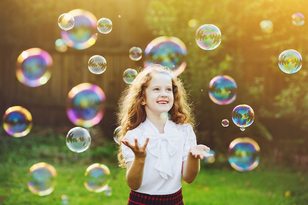 Criança bonita que aprecia soprando bolhas de sabão no verão na natureza.