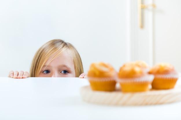 Criança bonita que come o pequeno almoço em casa.