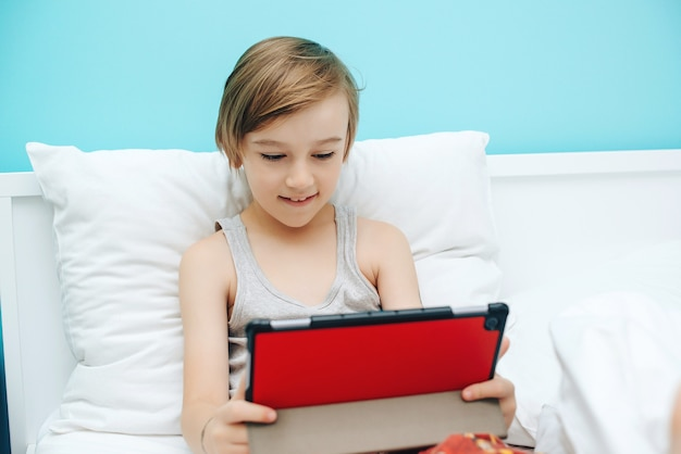 Criança bonita usando dispositivo digital na cama antes de dormir. menino assiste a vídeos e joga no tablet. dependência das crianças da internet e dos gadgets.