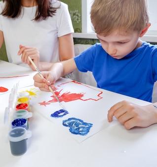 Criança bonitinha desenha à mesa com tintas com sua mãe closeup sala de jogos