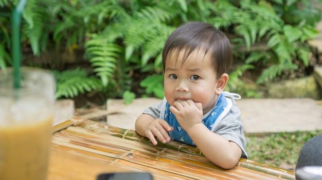 Criança bonito asiática que come um petisco em um jardim.