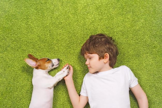 Criança bonito que abraça o jaque do cachorrinho