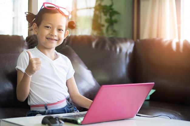 Criança bonito que joga o computador em casa com alargamento claro. foco seletivo.