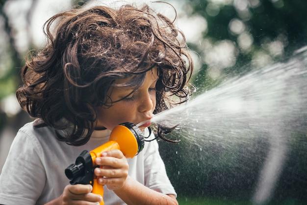 Criança brinca com água no quintal do jardim