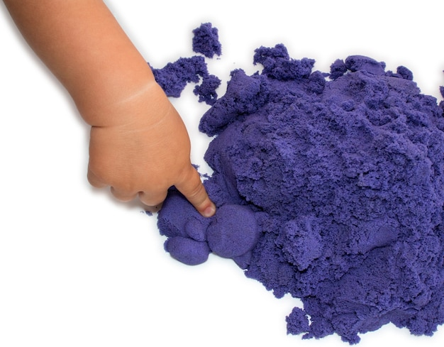 Criança brinca com areia cinética de cor roxa brilhante isolada em fundo branco