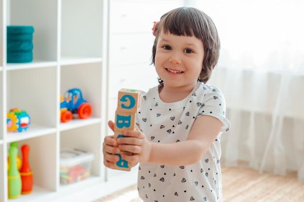 Criança brinca com blocos de madeira com letras no chão da sala uma menina está construindo uma torre em casa ou no jardim de infância.