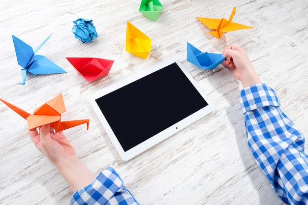 Criança brinca com tablet e origami.