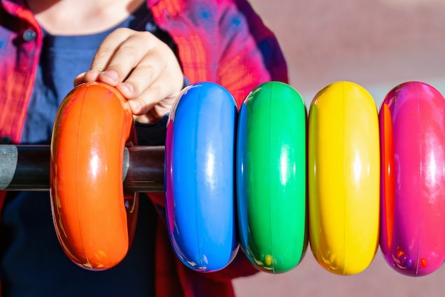 Criança brinca com um brinquedo educacional no parquinho, close-up.